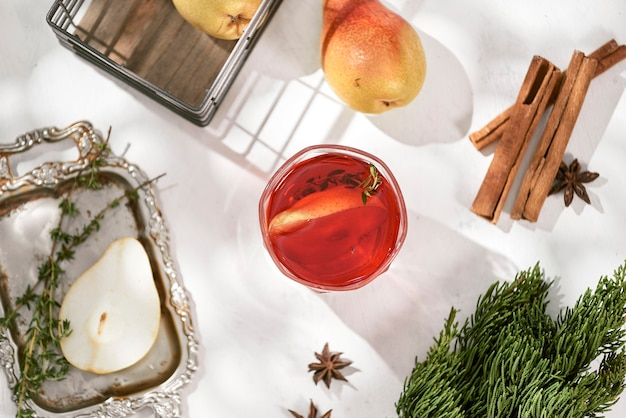 Delicious spicy hot mulled red wine with cinnamon, star anise and slice pear served in a carafe and glass for a cold winter evening or festive christmas beverage