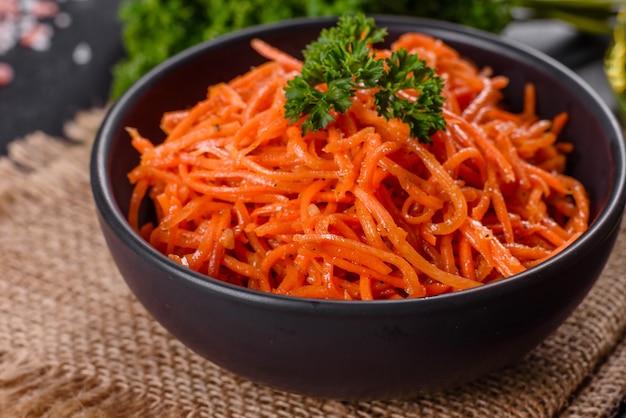 Вкусная пряная сочная яркая корейская морковь в керамической посуде на темном бетонном фоне. азиатская кухня