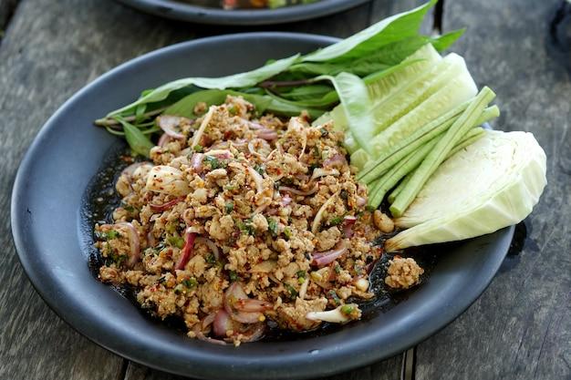 나무 테이블에 접시에 신선한 야채와 함께 맛있는 매운 돼지고기 샐러드