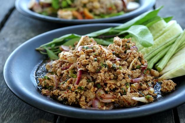 나무 테이블에 있는 접시에 신선한 야채를 곁들인 맛있는 매운 돼지고기 샐러드