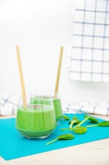 Вкусный пюре из шпината, изолированные на белом фоне. элегантные стеклянные бокалы с коктейлями и бамбуковые экологически чистые трубки для питья. листья шпината. концепция здорового питания, здорового образа жизни.