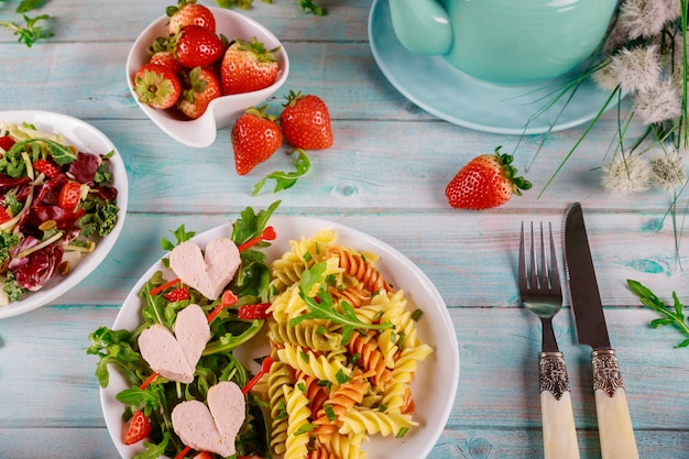 Delicious spiral pasta rotini, green salad with sausages and strawberries