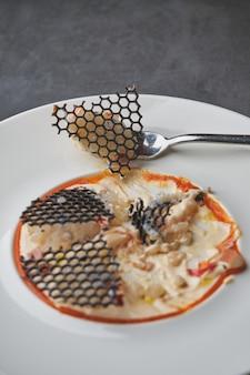 エレガントなイカ墨の格子が付いたおいしいイカのカルパッチョ