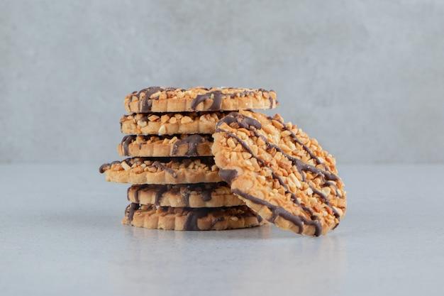大理石の背景にチョコレートで飾られたクッキーのおいしいスタック。