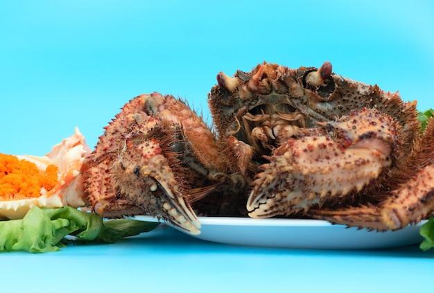 Вкусный краб на пару лежит на белой тарелке на синем фоне с оранжевой крабовой икрой и зеленым салатом