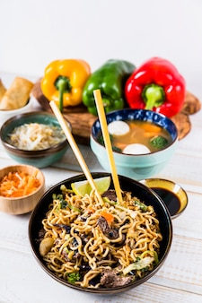 Delicious stir fry noodles with beef on chopsticks with soup bowl over the wooden desk