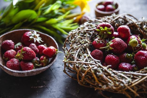 ヴィンテージの花輪の濃い灰色のテーブルに黄色い花とおいしいイチゴ。健康食品、果物