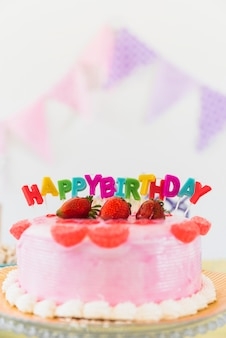Delicious strawberry birthday cake with colorful candles