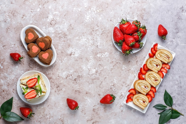 Delicious strawberry cake roll, heart shaped cookies, cake slices with fresh strawberries, top view