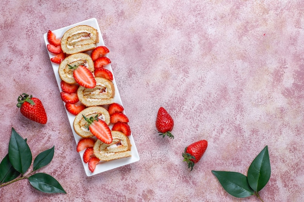 Delicious strawberry cake roll with fresh strawberries, top view