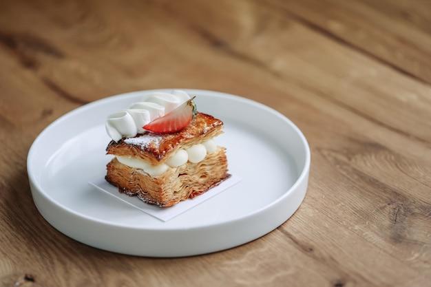 木製のテーブルにホイップクリームとおいしいストロベリーケーキ。イチゴのミルフィーユ。