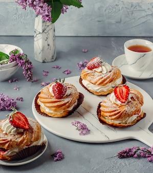대리석 보드에 맛있는 딸기 크림 퍼프 eclairs