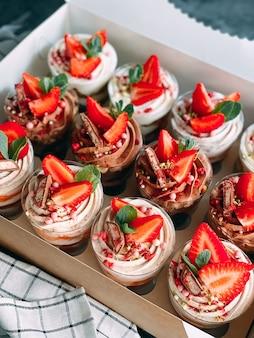 흰색 상자와 주방 옷에 맛있는 딸기 디저트