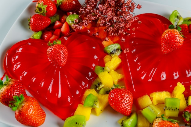Delicious strawberry gelatin dessert heart shape with flowers for couple
