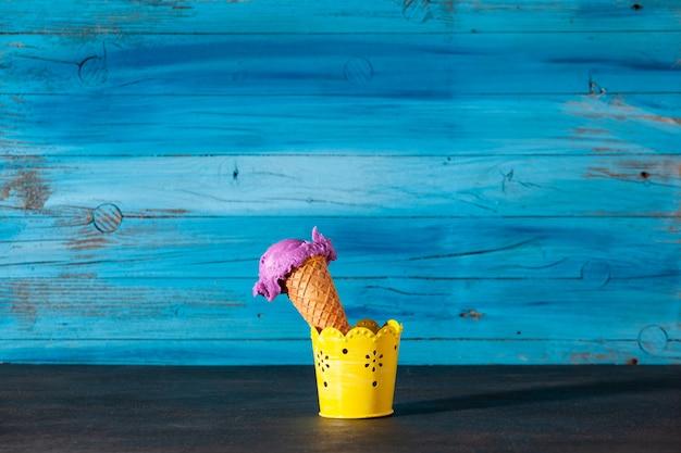 오래된 나무 파란색 벽에 맛있는 딸기 아이스크림 콘