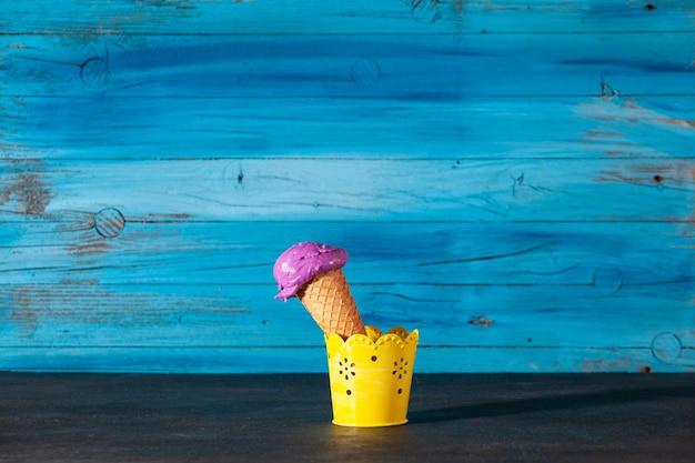 Вкусный рожок клубничного мороженого на старой деревянной синей стене