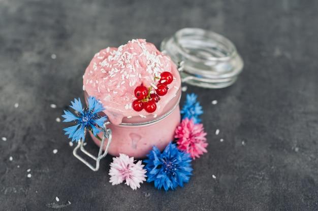 Вкусное клубничное мороженое, украшенное кокосовой стружкой, красной смородиной и голубыми васильками на сером фоне. вкусный десерт. концепция питания