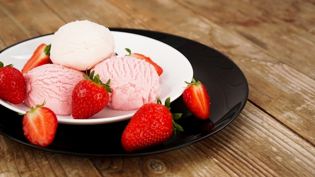 Delicious strawberry ice cream with fresh strawberrieson a white and black plate. tasty summer cold dessert. wood background