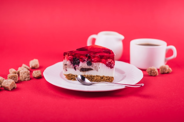 Delicious strawberry jelly and cheese cake on white plate with brown sugar cubes against red backdrop