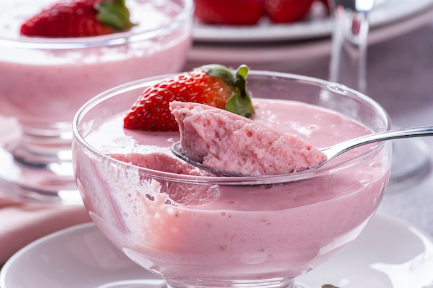 Delicious strawberry mousse in glass bowl with fresh strawberries.