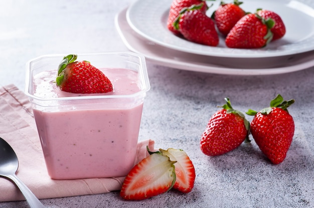 Delicious strawberry mousse in a plastic cup for delivery with fresh strawberries.