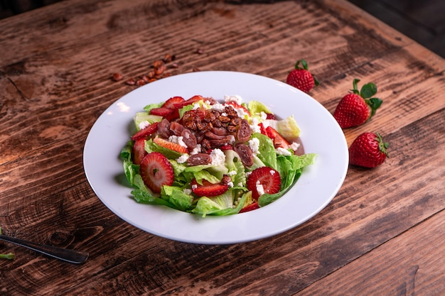 Вкусный клубничный салат с зеленым салатом и мясом в белой тарелке