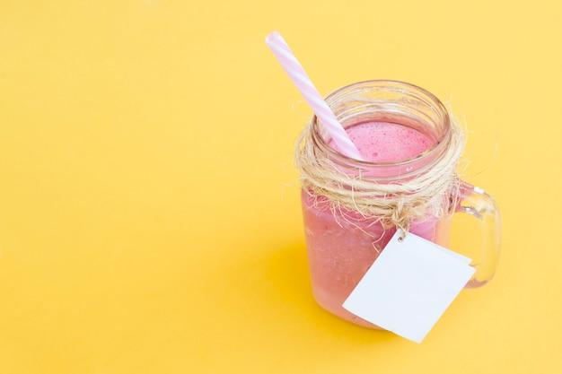 Delizioso frullato di fragole con paglia e etichetta per mock up con spazio a destra