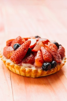 Delicious strawberry tart on wooden backdrop