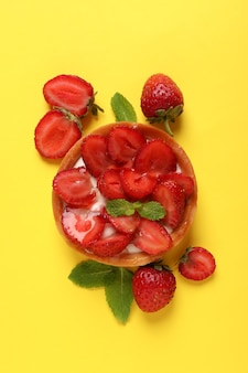 Delicious strawberry tart on yellow background, top view.