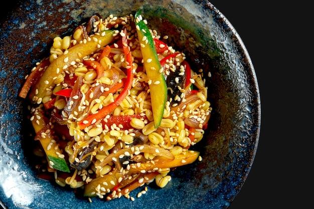 Вок с рисом вкусной уличной еды с овощами и арахисом в тарелке. классическая азиатская кухня. доставка еды. изолированные на черном
