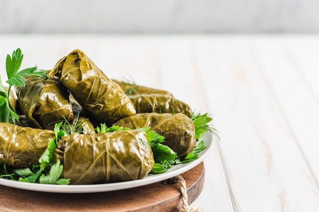 Delicious stuffed grape leaves on a black plate with fresh cilantro and dill