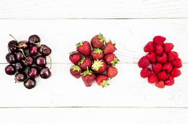 Delicious summer berries on white surface