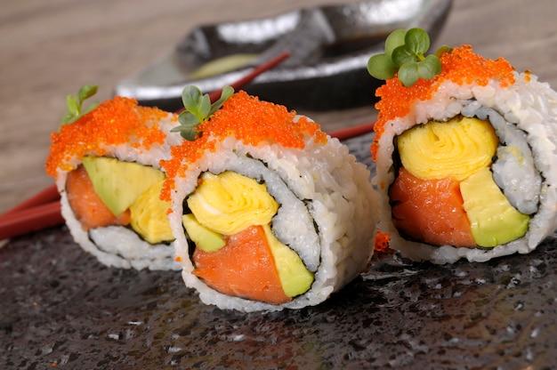 Rullo di sushi con il caviale su un piatto nero