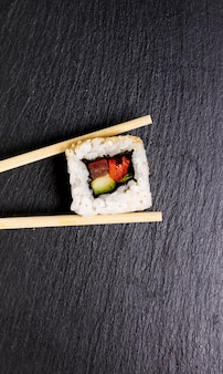 Delicious sushi on black plate