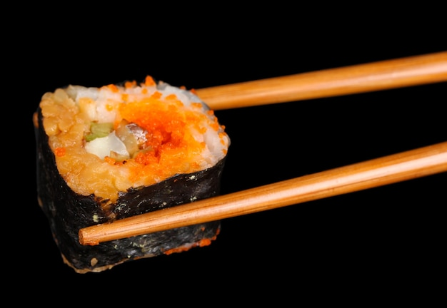 Delicious sushi and chopsticks on black surface