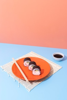 Delicious sushi on plate with chopsticks high angle