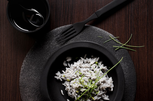 Delicious sushi rice on black plate with fork and soy sauce