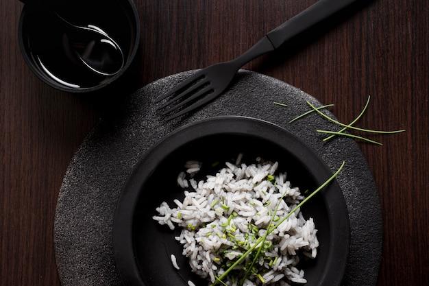Вкусный рис для суши на черной тарелке с вилкой и соевым соусом