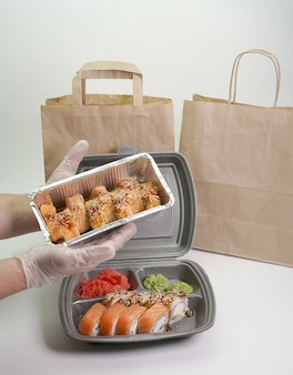 Delicious sushi rolls are served in foil packaging on an isolated white wall of the table