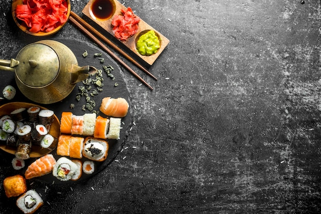 Delicious sushi rolls and fragrant green tea. on dark rustic background