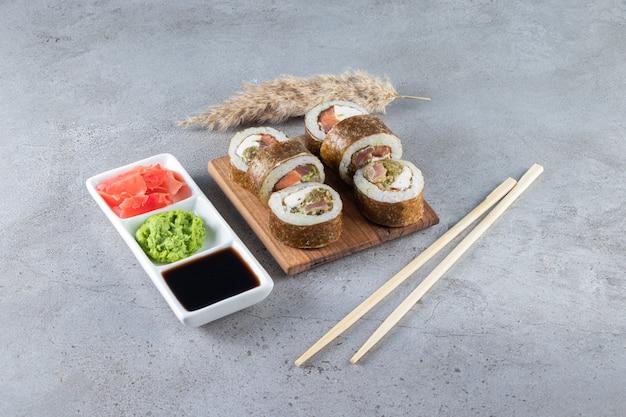Вкусные суши-роллы с тунцом и маринованным имбирем на каменном фоне.
