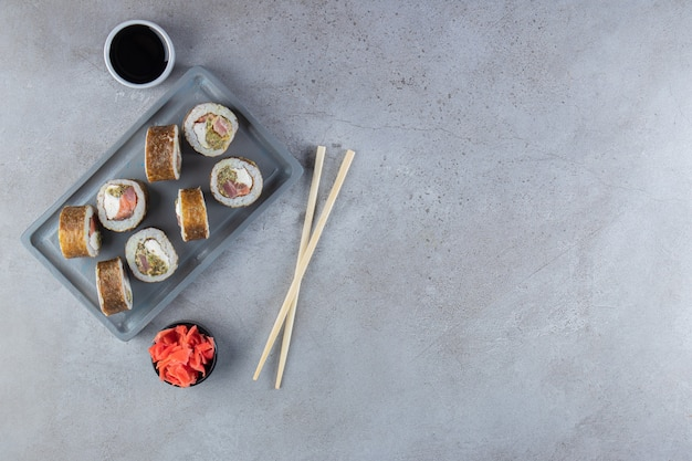 Delicious sushi rolls with tuna fish on dark plate.