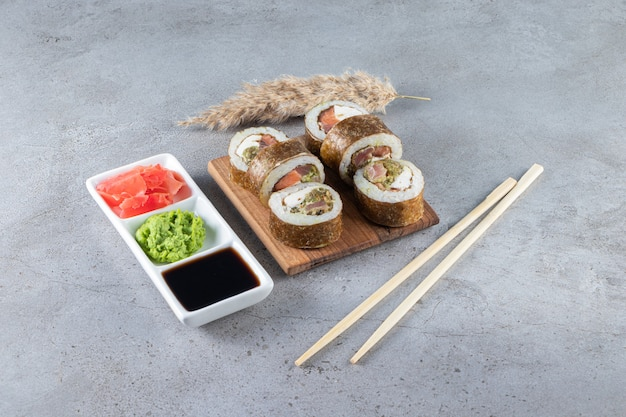 Delicious sushi rolls with tuna fish and pickled ginger on stone background.
