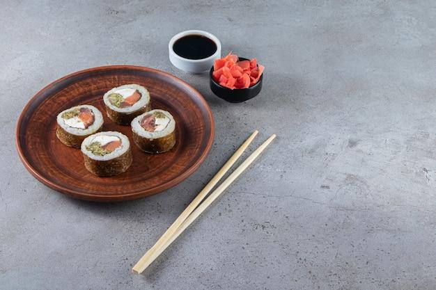 Deliziosi involtini di sushi con tonno sul tavolo di pietra.