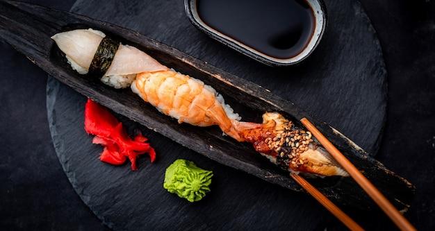 Вкусный набор суши сашими с креветками, имбирем и соевым соусом, подается с палочками для еды и васаби на б ...