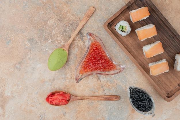 캐 비어, 생강, 바 사비 나무 접시에 맛있는 초밥.