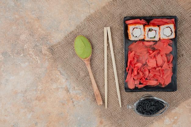 木の板にキャビア、生姜、わさびが入った美味しいお寿司