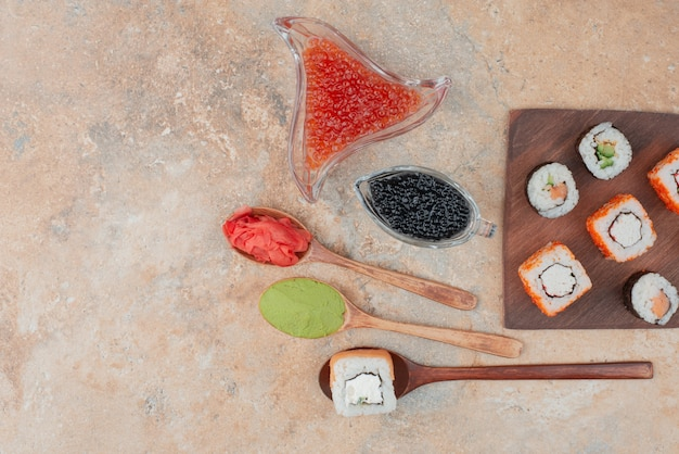 나무 접시에 캐 비어, 생강, 바 사비와 함께 맛있는 스시