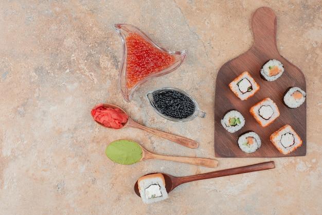 木の板にキャビア、生姜、わさびが入った美味しいお寿司。