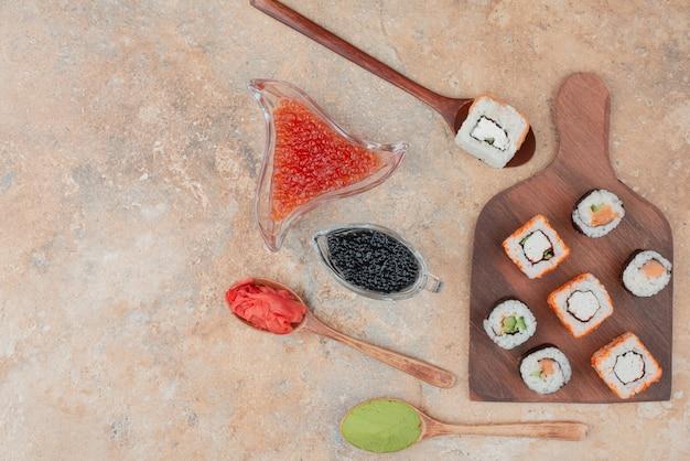 Delizioso sushi con caviale, zenzero e vasabi sul piatto di legno.